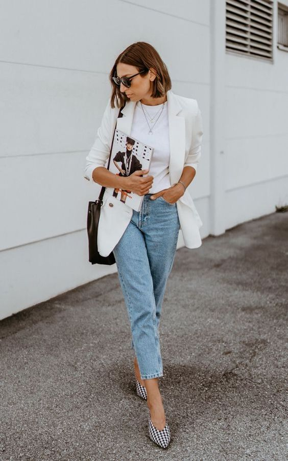 a trendy summer outfit with a white tee, light blue jeans, an oversized white blazer and plaid slingbacks