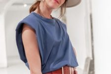 a vacation look with a blue padded shoulder tee, white pants, a red belt, a white hat and statement earrings