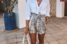 a vacation outfit with a white shirt, snake print shorts, a white hat, brown slippers and a macrame bag
