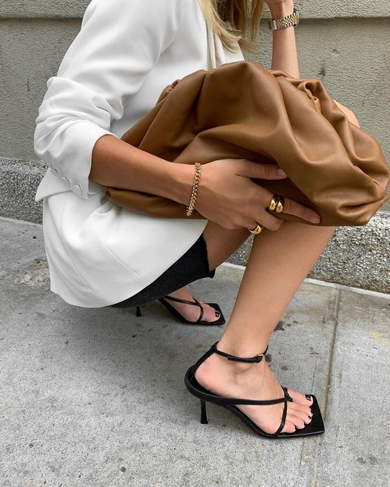 a white blazer, black shorts, black square toe sandals and a brown oversized clutch for a minimalist look