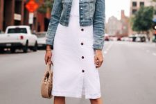 a white button up knee cotton dress, a blue denim jacket, tan block heels and a wicker bag