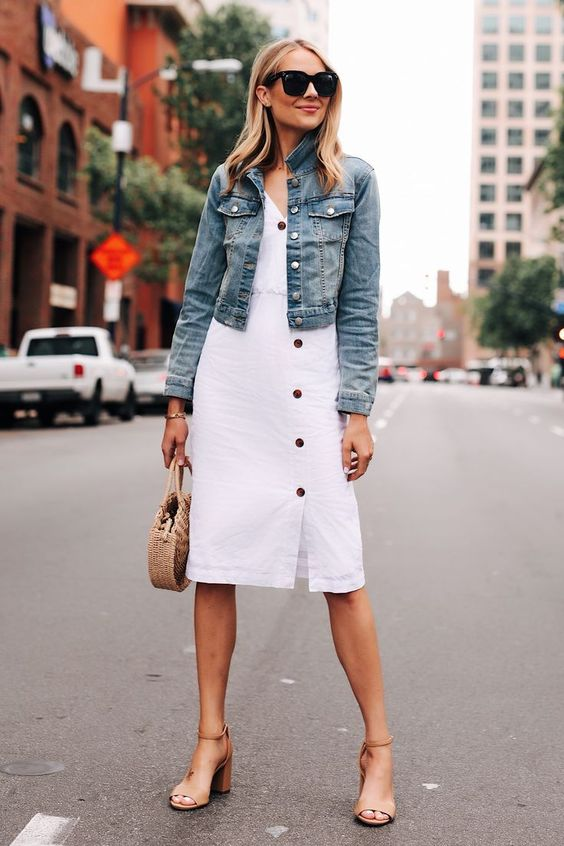 a white button up knee cotton dress, a blue denim jacket, tan block heels and a wicker bag