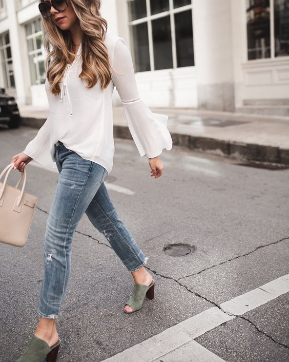 a white chiffon blouse with bell sleeves, blue jeans, green heeled mules and a tan bag