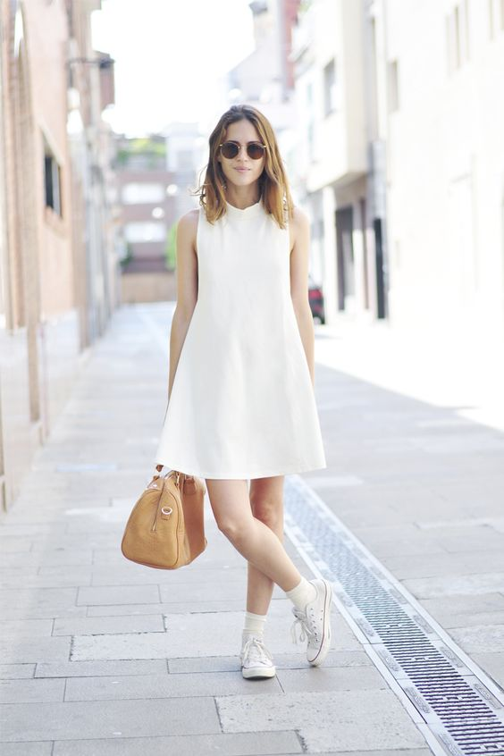 a white cotton mini A line dress with a high neckline and no sleeves, white sneakers and a tan bag