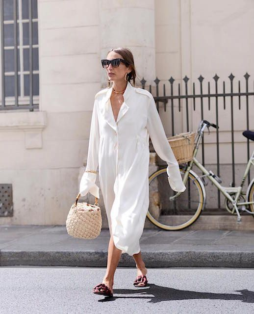 a white cotton shirtdress, burgundy slippers, a basket bag and statement gold accessories