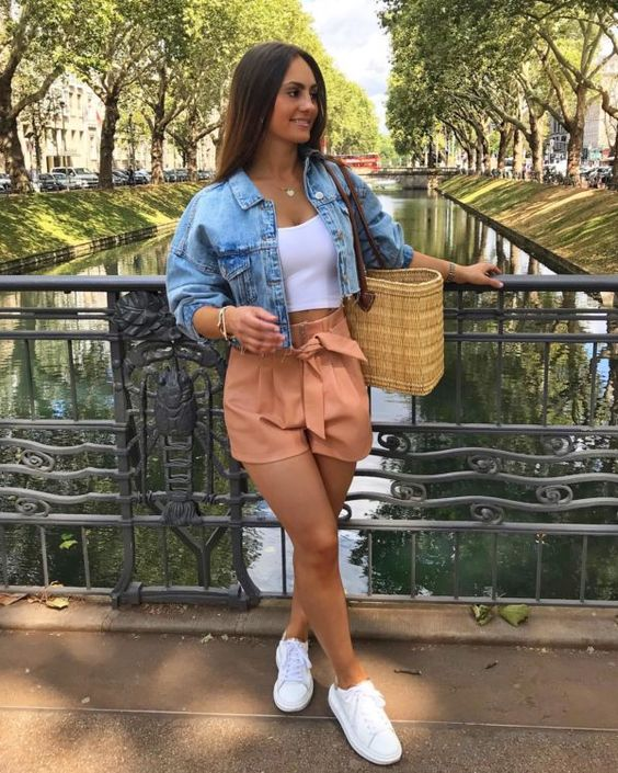 a white crop top, a blue cropped dneim jacket, peachy shorts, white sneakers and a woven bag for summer