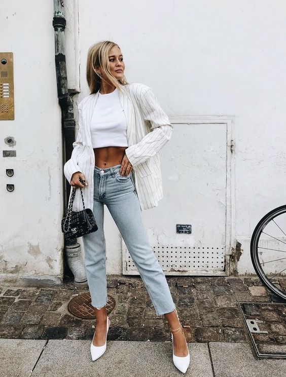 a white crop top, neutral cropped jeans, white pointed toe shoes and a striped blazer
