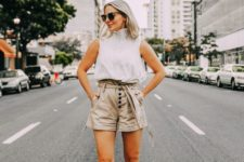 a white high neckline sleeveless top, neutral paper bag shorts and grey peep toe shoes
