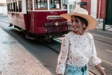 a white lace shirt with long sleeves, blue denim shorts, a woven bag and a wide brim hat for summer