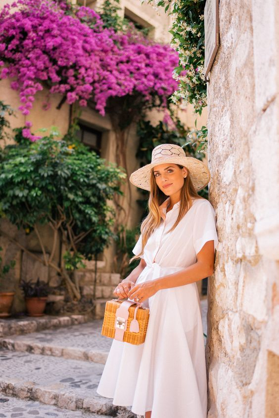 a white midi shirtdress with short sleeves, a vintage inspired basket bag and a chic hat