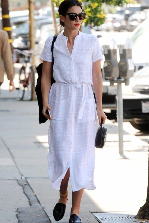 a white midi shirtdress with short sleeves, pockets, black slipper mules and a black bag