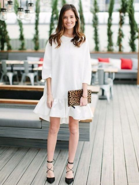 a white over the knee voluminous dress with a ruffle edge, short sleeves, black lace up heels and an animal print clutch
