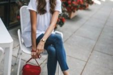 a white oversized t-shirt, blue cropped skinnies, red slingbacks and a red bag plus statement earrings