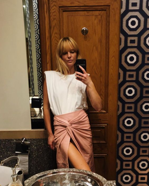a white padded shoulder t shirt and a pink draped midi skirt for a summer look