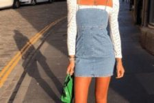 a white printed blouse with puff sleeves, a denim mini dress, white sneakers and a green bag