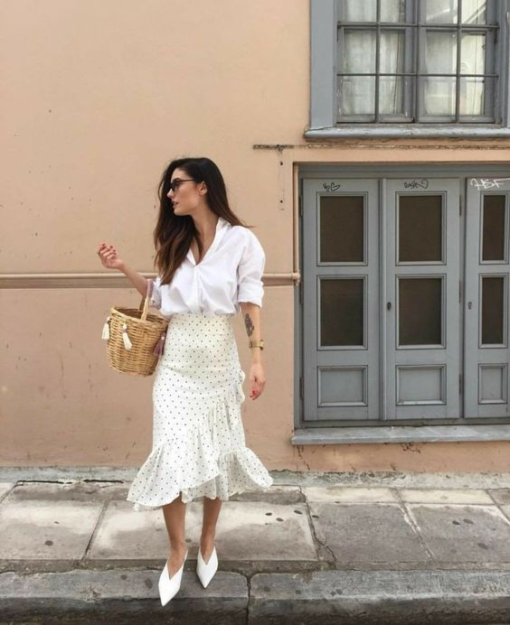 a white shirt, a polka dot ruffle midi skirt, white pointed toe heels and a basket bag