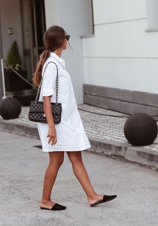 a white shirtdress, black slippers and a black bag for a chic minimalist look