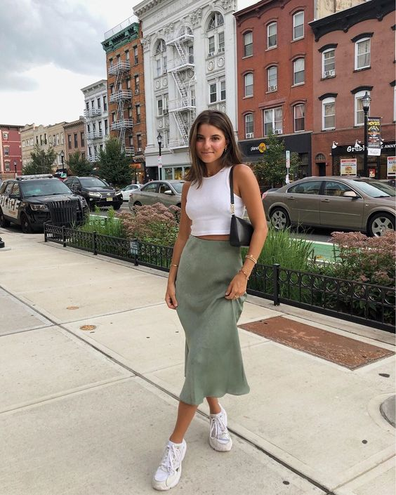 a white sleeveless crop top, a green suede midi skirt, white trainers and a black baguette bag
