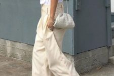 a white sleeveless top, neutral cargo pants with pockets, white square toe sandals, a small woven leather bag