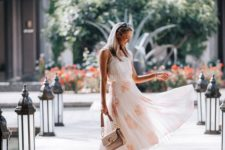 a white spaghetti strap top, a midi floral pleated skirt, spiked block heels and a blush bag