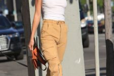 a white tank top, tan cargo pants, white trainers and a brown bag by Kendall Jenner