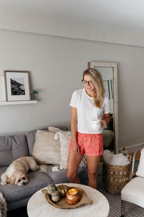 a white tee and coral shorts are all you need to wear at home in summer to look bright and cool