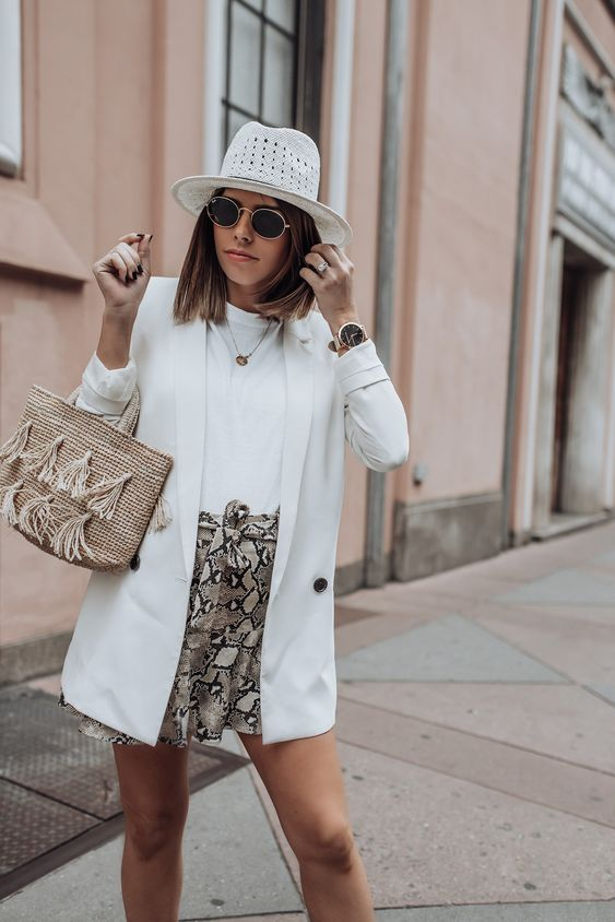 a white tee, snake print mini shorts, a white blazer, a woven bag and a white hat for a cool summer day
