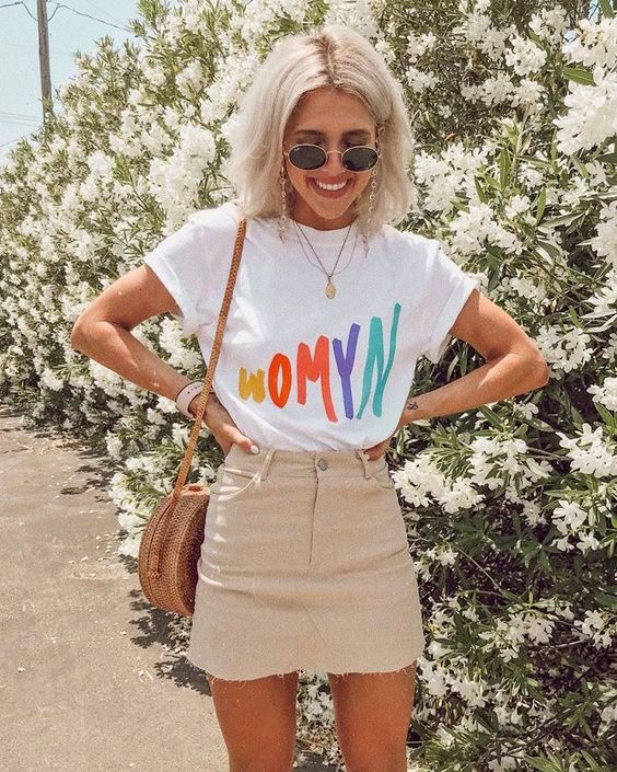 a white tee with a bright print, a tan mini skirt, a round wicker bag for a bright summer look