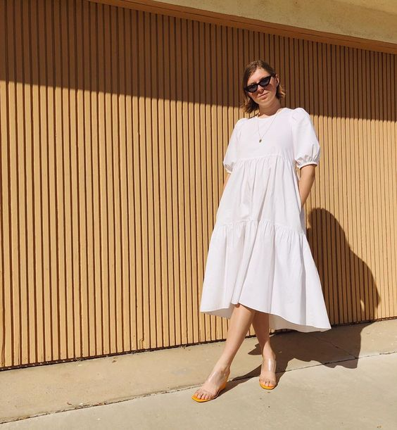 a white voluminous cotton midi dress with a high neckline, puff sleeves and sheer heeled mules