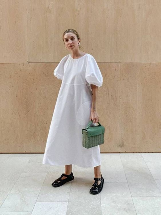 a white voluminous cotton midi dress with pockets and puff sleeves, black shoes and a green bag