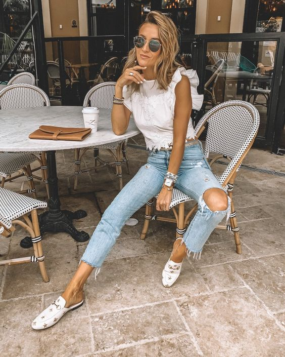 cropped ripped blue skinnies, a white lace crop top with ruffle sleeves, white slipper mules