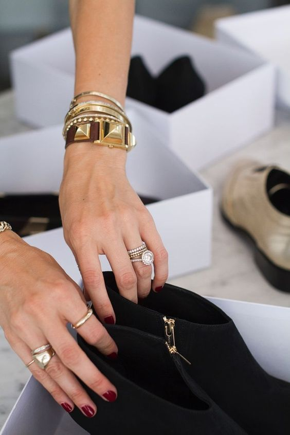 stacked gold and silver bracelets and a statement gold and brown leather one plus gold rings for a statement look