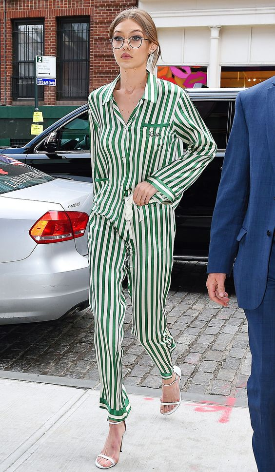 Gigi Hadid in a green and white striped pajamas suit, white heels and glasses