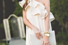 With beige clutch and oversized sunglasses