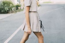 With beige shirt, mini skirt and black and white bag