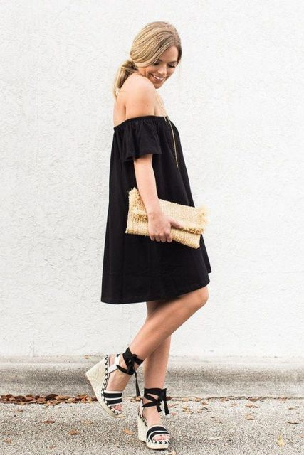 With black off the shoulder loose dress and beige clutch