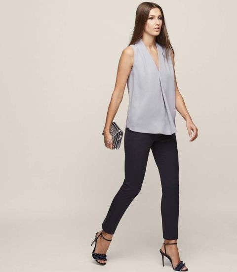 With black skinny pants, embellished clutch and black high heels