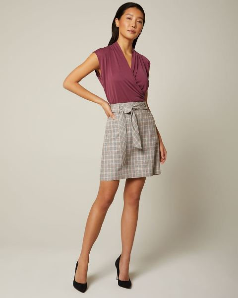 With checked belted mini skirt and black pumps
