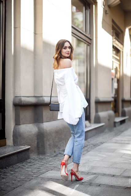 With cropped jeans, red high heels and mini bag