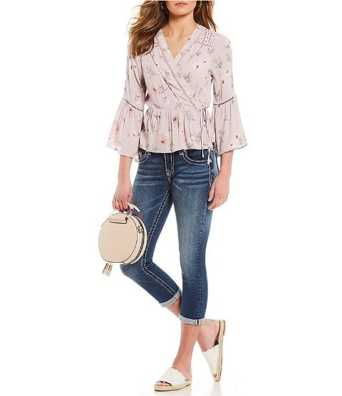 With cuffed jeans, white flat mules and rounded bag