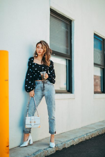 With cuffed jeans, white shoes and bag