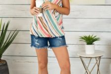 With denim shorts and gray sandals
