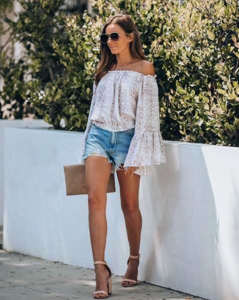 With denim shorts, beige clutch and beige ankle strap shoes
