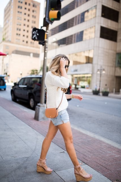 With denim shorts, white shirt and brown mini bag