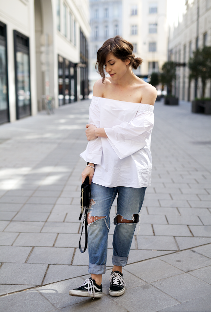 With distressed cuffed loose jeans, black and white sneakers and black bag