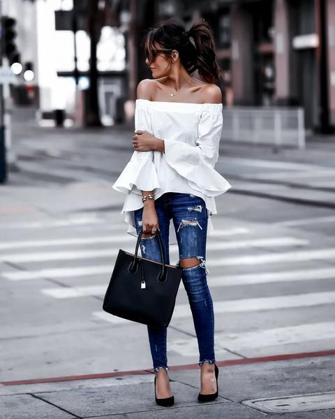 With distressed jeans, black tote bag and black pumps