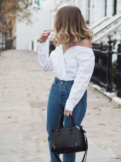 With high-waisted jeans and black bag