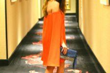 With orange mini dress and sandals