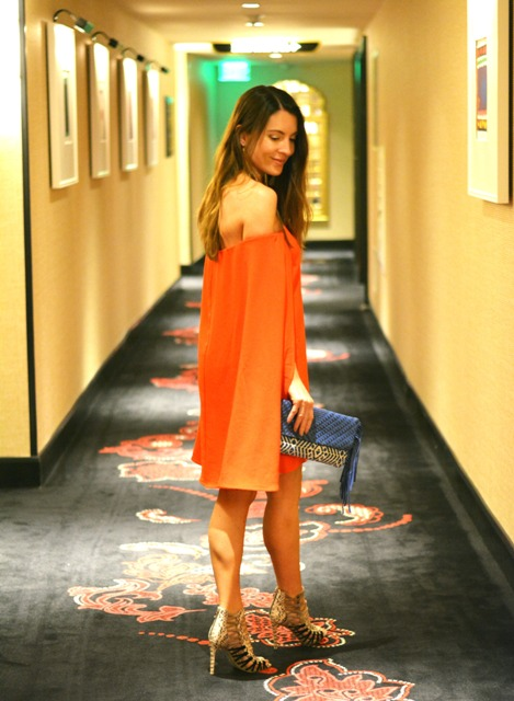 With orange mini dress and sandals