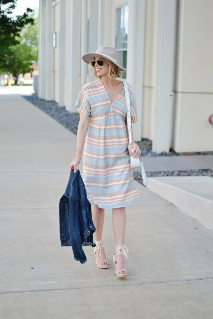 With pastel colored V-neck dress, hat, denim jacket and white bag
